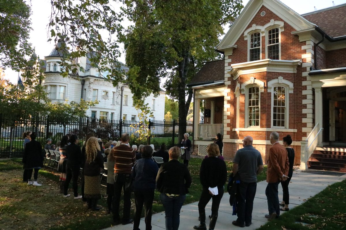 A two-story, red brick building with a crowd gathered.