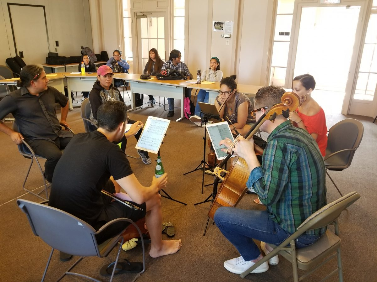 An image of musicians sitting in a circle reading sheet music.