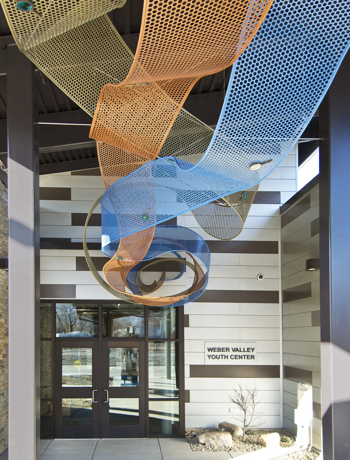 A image of an outdoor, metal sculpture resembling yellow, orange, and blue ribbons.