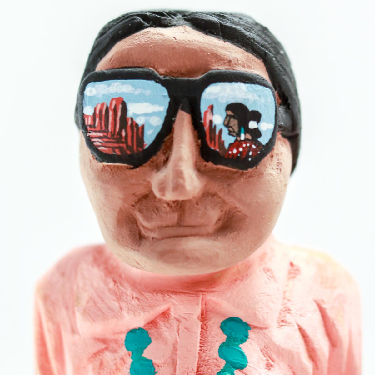 A wooden sculpture of a man wearing sunglasses.
