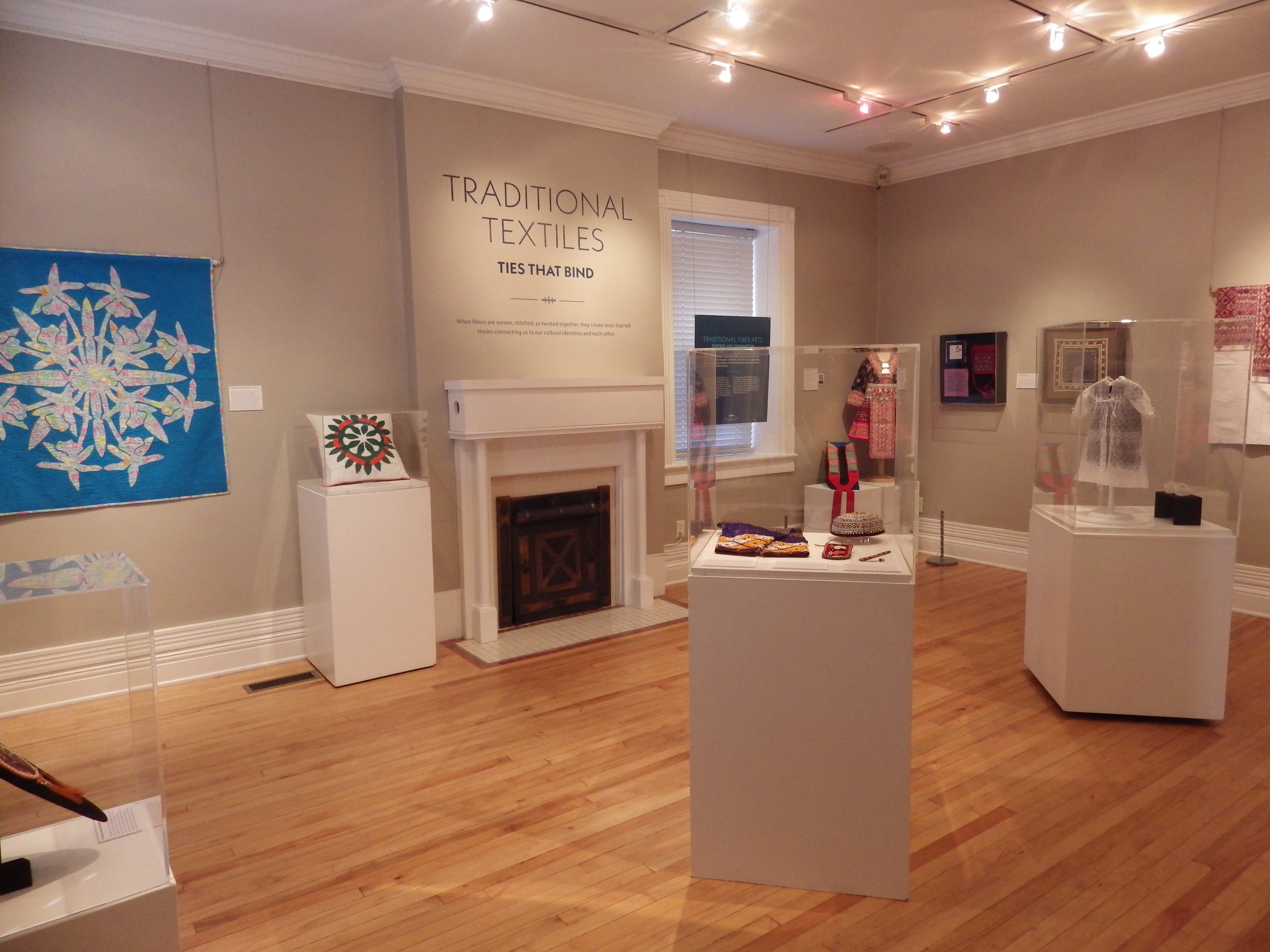 """An image of an art gallery with the words """"Traditional Textiles: Ties that Bind"""" on the wall."""