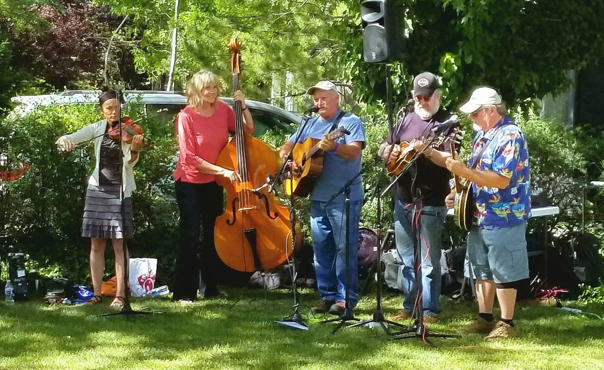 A group of five musicians plays music in a green, leafy outdoor setting.
