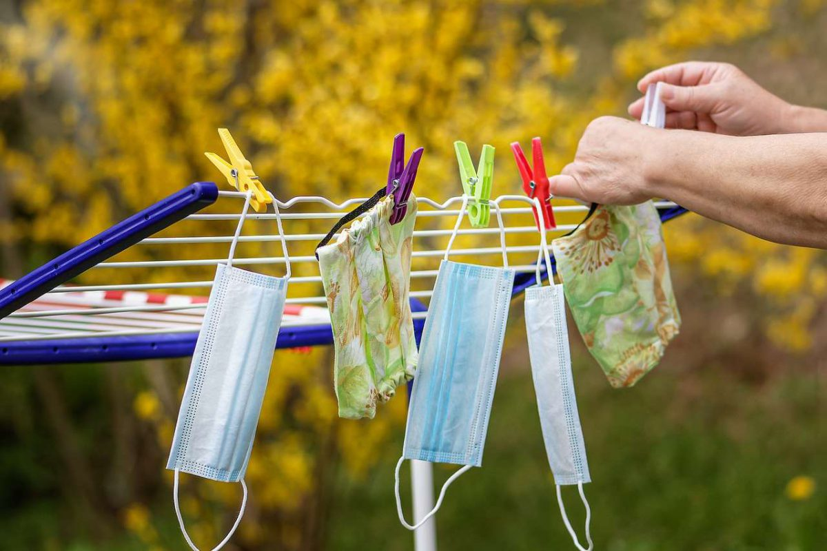 An image and two hands attaching face masks to a wire with clothespins.