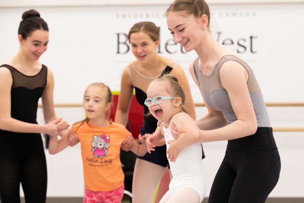 A photo of three teenage ballerinas with two younger girls.