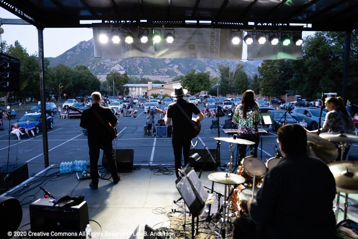 A band plays on a stage at a parking lot concert. Viewers are spread apart sitting in or around their cars.