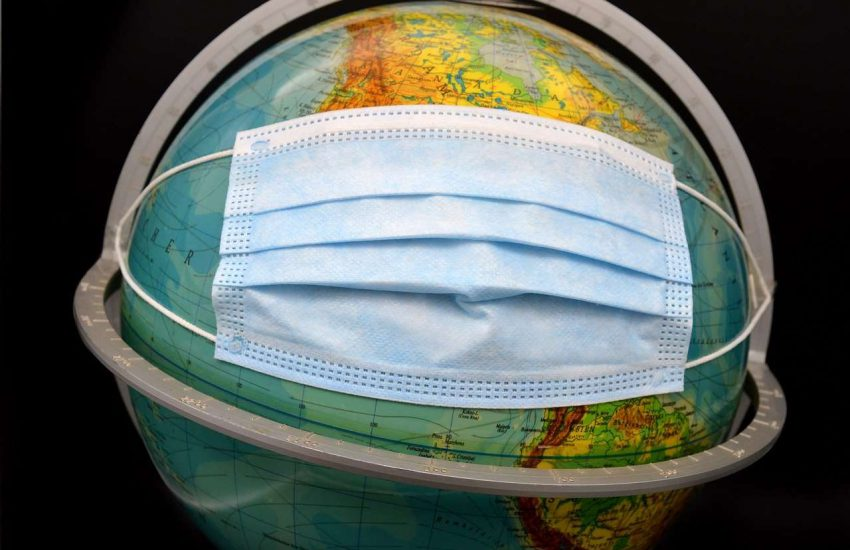 An image of a world globe with a blue surgical mask attached as though it is being worn.