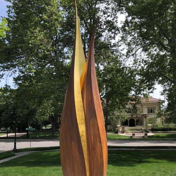 A brown and gold metal sculpture of a sego lily in an outdoor setting.