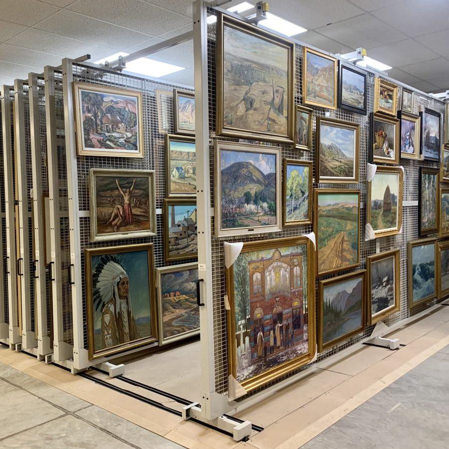 Framed artworks are neatly displayed on vertical storage racks.