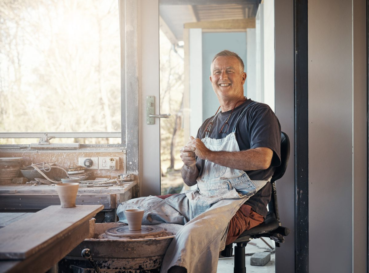 A white man wearing a dark grey shirt and white apron with short blond hair sits making pottery.