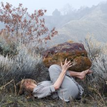 A white woman with blond hair lays on the ground surrounded by bushes, holding a rock.