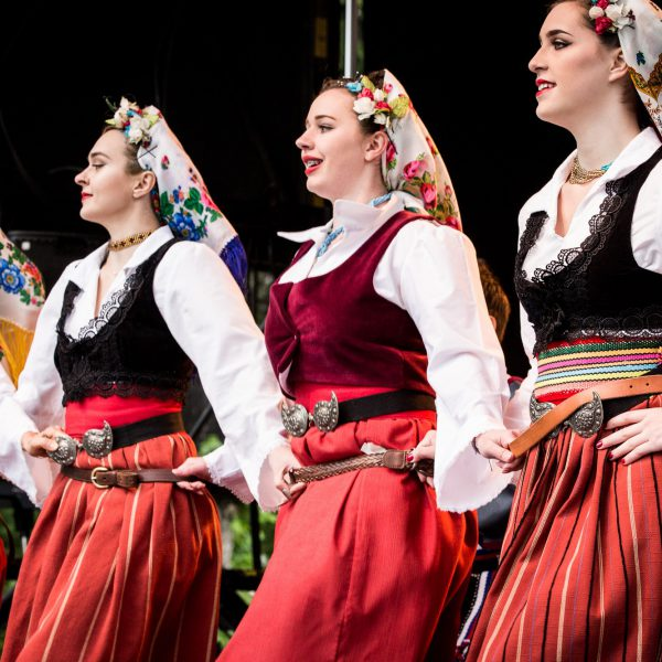 Three women perform a folk dance wearing white blouses, red skirts, and colorful headscarves.