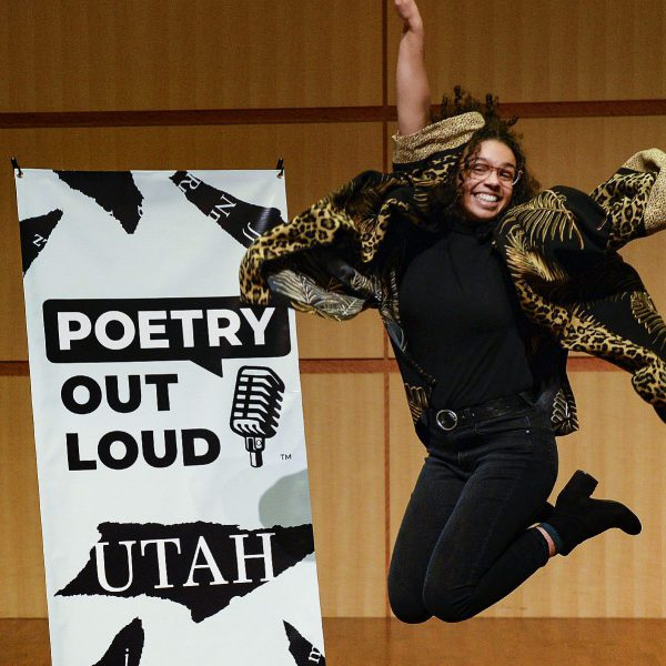 """A girl wearing all black with curly black hair jumps and poses next to a sign that says, """"Poetry Out Loud Utah."""""""