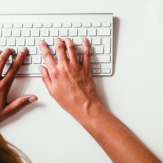 Hands writing on a computer keyboard.