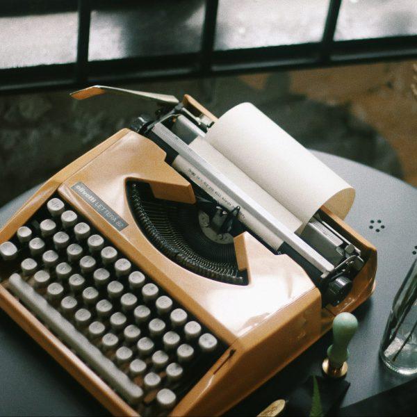 An orange typewriter sits on a dark table.