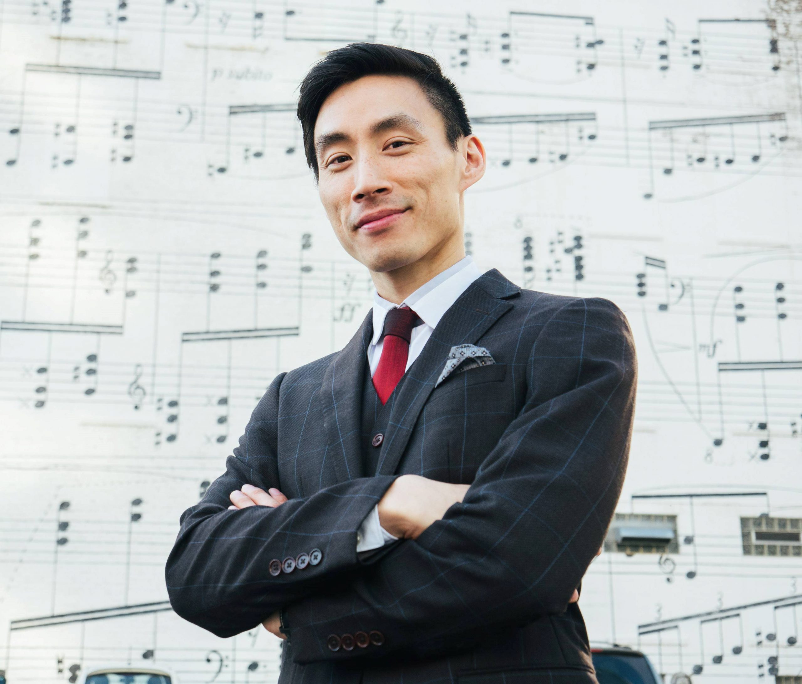 An Asian man wearing a suit with his arms folded in front of large sheet music.