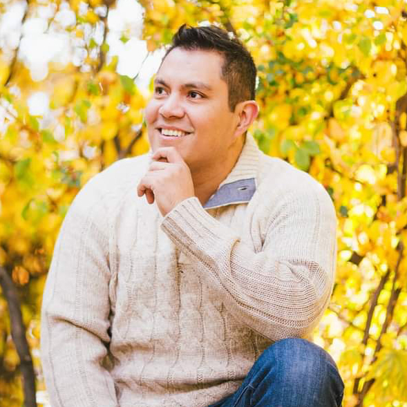 A photo of a man wearing a cream sweater in front of trees with yellow leaves.