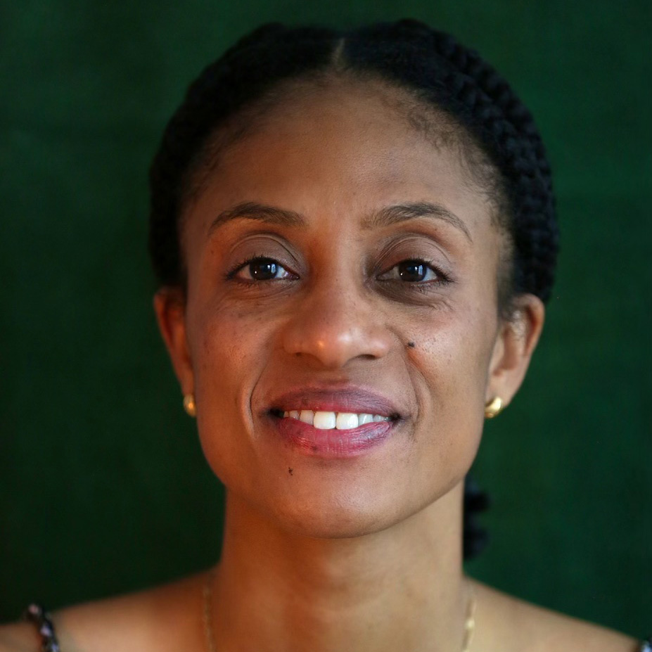 A photo of a Black woman in front of a green background.