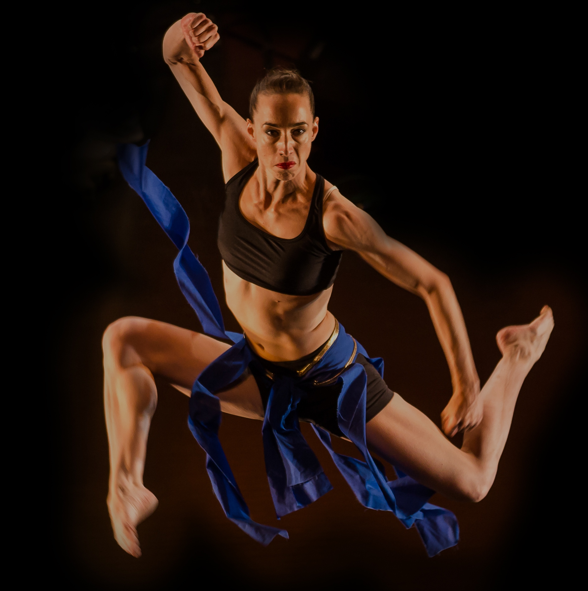 A photo of a white woman wearing blue strips of fabric, dancing.
