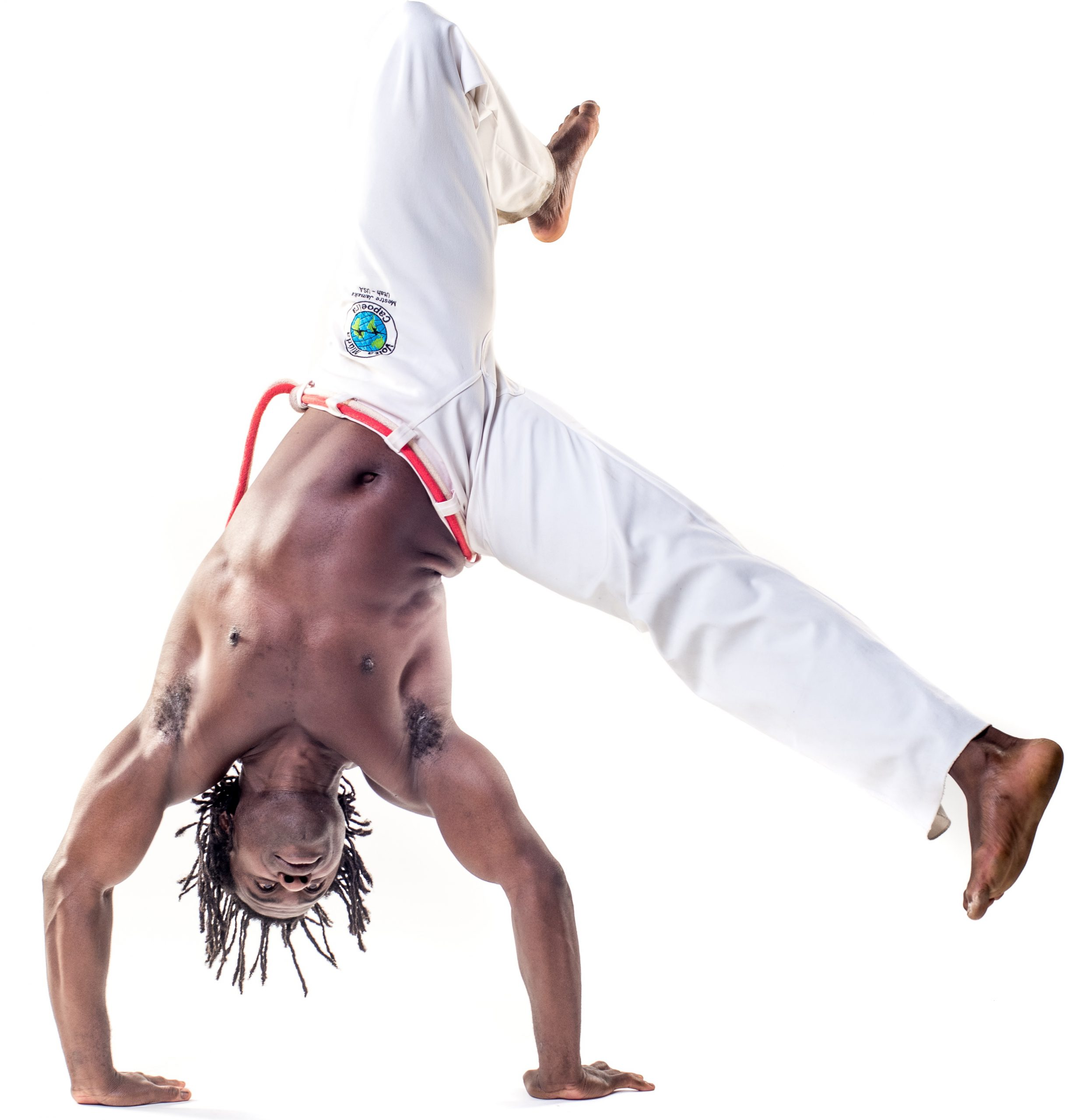 A photo of a shirtless Black man wearing white mans, doing a handstand.