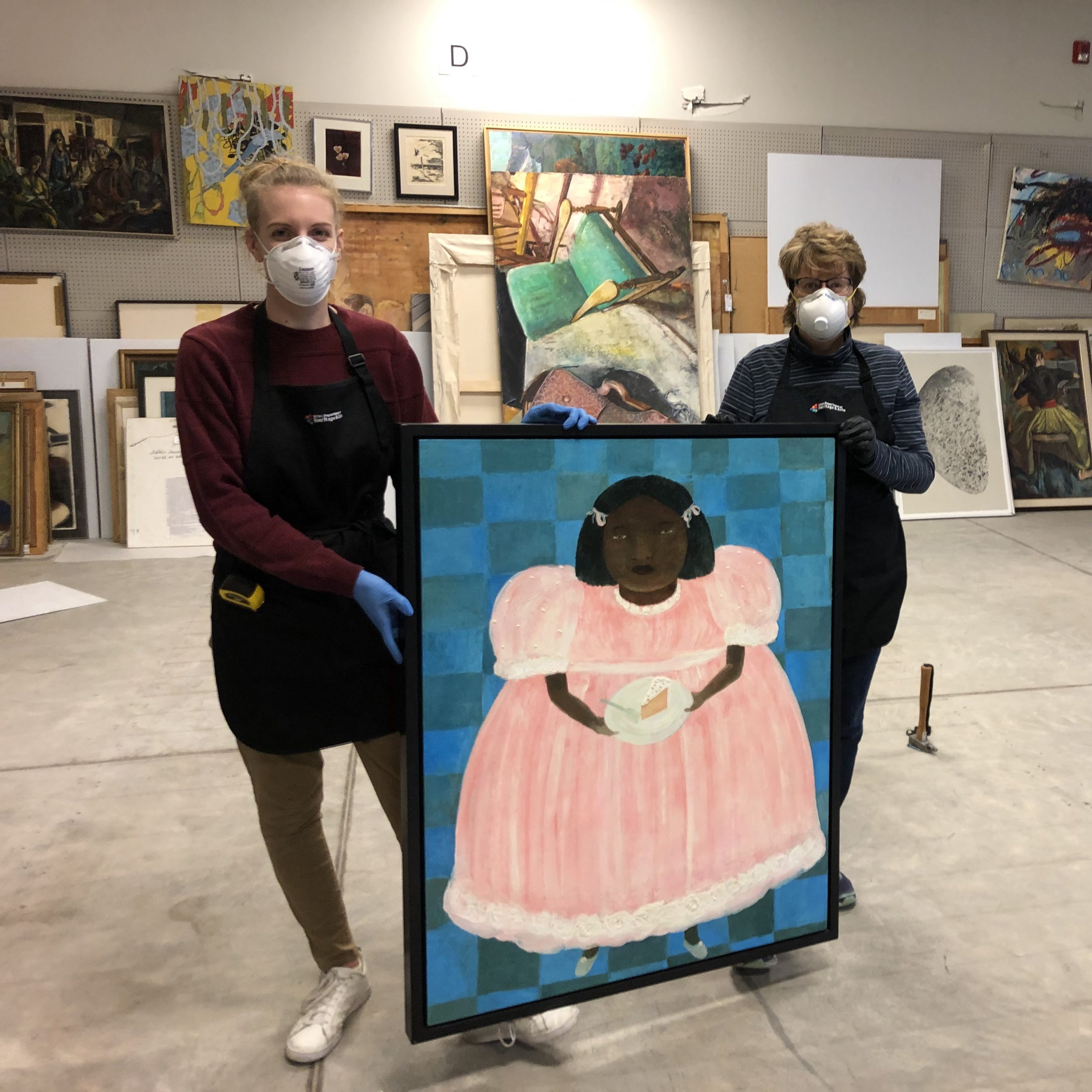 Two women, wearing white face masks, stand holding a painting of a brown-skinned girl wearing a pink dress, holding a white piece of cake on a plate.