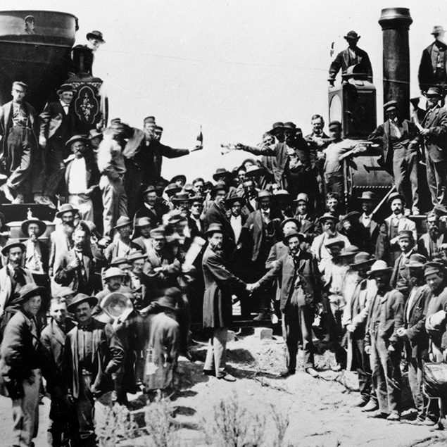 A black-and-white photo of a large crowd standing around two trains at the completion of the transcontinental railroad.