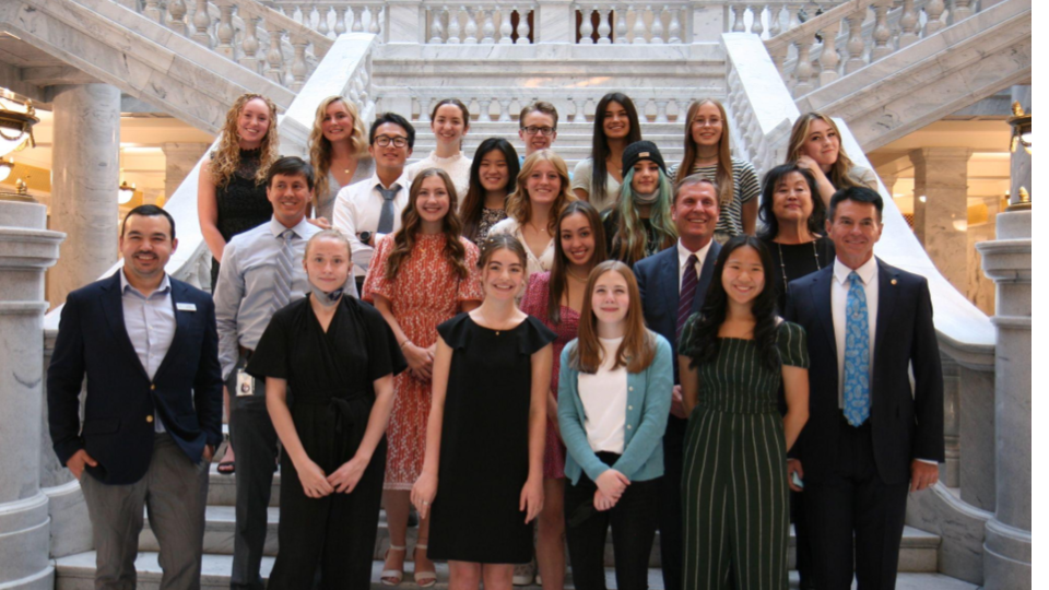 Students and legislators stand on a staircase in the Utah State Capitol.