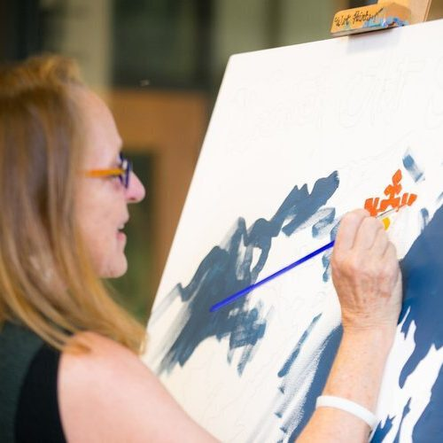 A woman painting on a canvas.