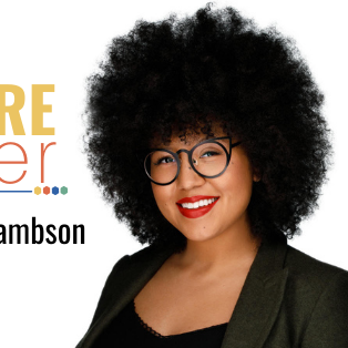 A Black woman wearing black glasses and a black blazer with a black afro.