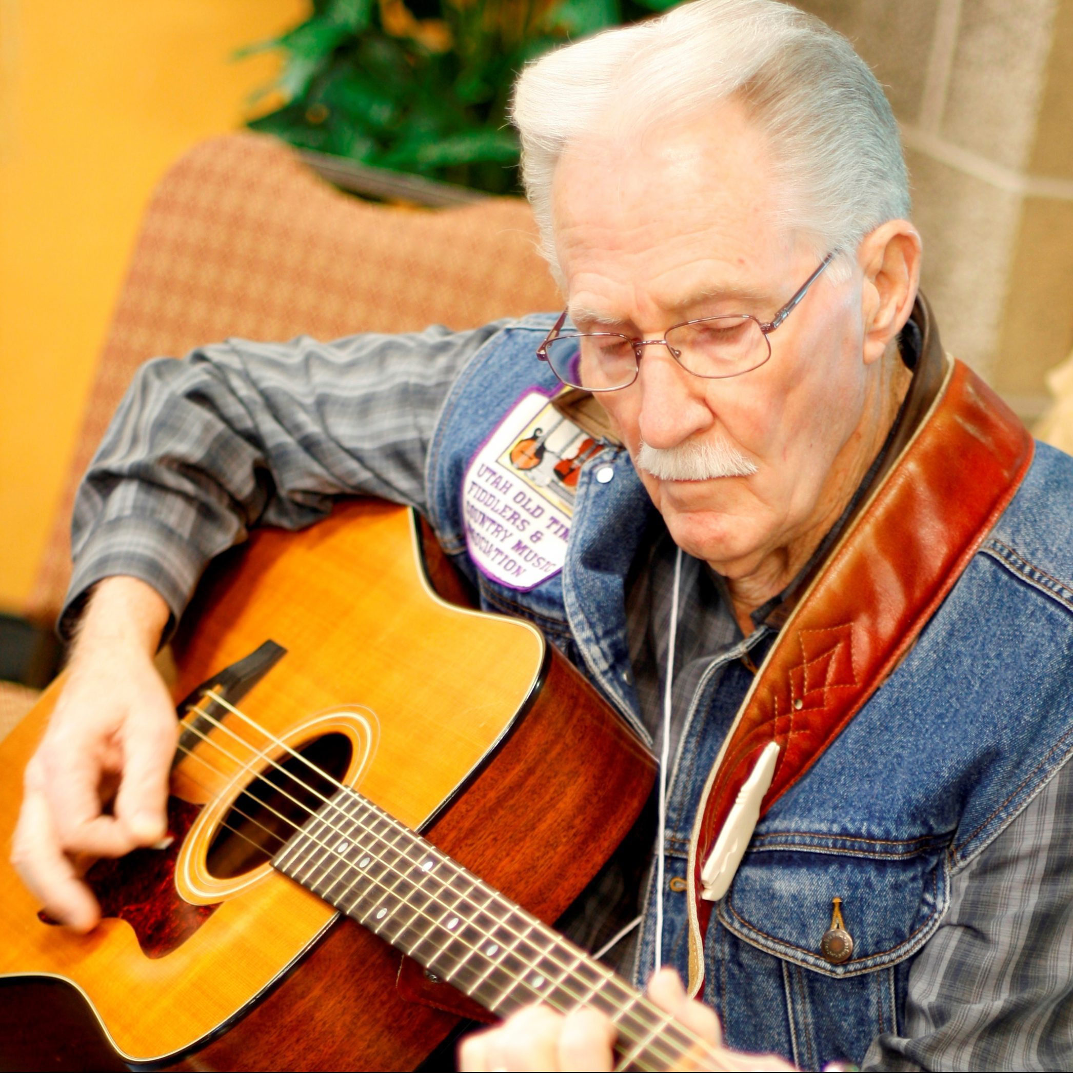 A senior man with short, white hair, a mustache, and glasses sits playing a guitar.