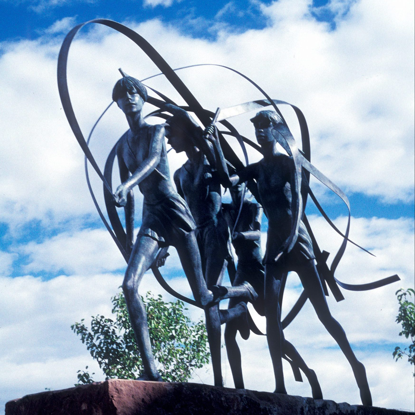 A metal sculpture of four people dancing and twirling ribbons.