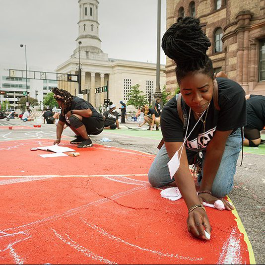 A group with a Black woman in the foreground drawing with chalk on a street.